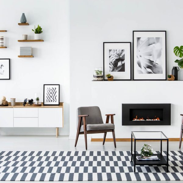 Fireplace between grey armchairs in modern living room interior with posters. Real photo